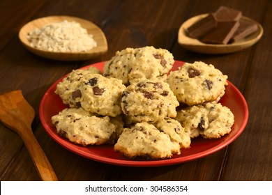 Homemade oatmeal and chocolate cookies on red plate with ingredients in the back, photographed with natural light (Selective Focus, Focus on the front of the cookies on the top)