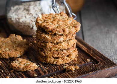 Homemade oatmeal cookies on wooden board on old table background. Healthy Food Snack Concept. Copy space/