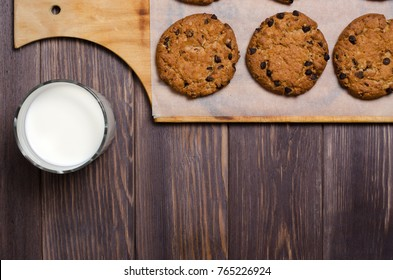 Homemade oatmeal cookies on a wooden cutting Board and milk. Wooden background. Flat top view