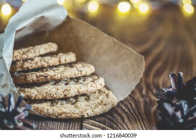 Homemade Oatmeal cookies in a pastry paper bag baking on a wooden rustic table Winter holiday still life Christmas or New Year card