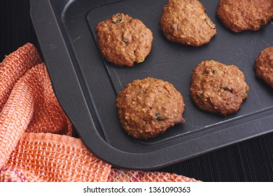 Homemade oatmeal cookies with raisins in a baking tray. Low key.