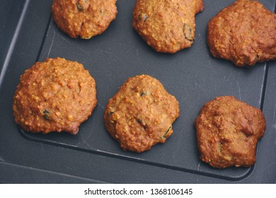 Homemade oatmeal cookies with raisins in a baking tray. Close up.