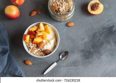 Homemade oatmeal granola with yogurt and peaches in bowl for healthy breakfast. Cereal and fruit breakfast bowl with yogurt.