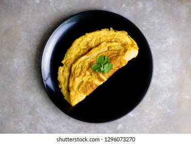 homemade omelette with coriander. isolated on black dish with grey cement background.