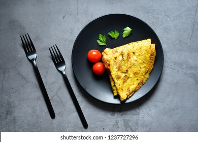 Homemade  omelette from organic eggs,  cherry tomatoes and fresh parsley.  Dark plate and forks.