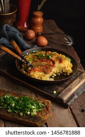 Homemade omlette with potato and green onion on a wooden rustic table. Space for text