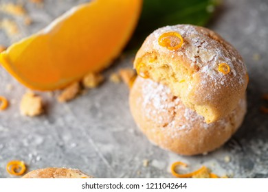 Homemade orange crinkle cookies with powdered sugar icing on gray background, close up