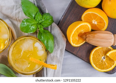 Homemade orange juice with ice cubes and basil leaves in glass on board