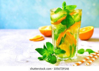 Homemade orange lemonade with mint in a tall glass on a blue slate, stone or concrete background.