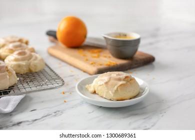 Homemade Orange Rolls on Marble Kitchen Counter with Wire Rack, Orange Juice, and Orange Zest