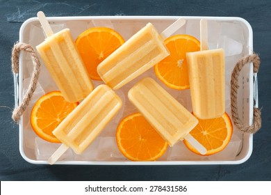 Homemade orange yogurt popsicles in an rustic ice filled tray with fresh fruit slices