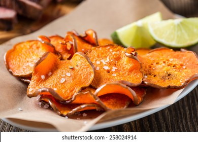 Homemade organic baked pumpkin chips served with lime wedges on kraft paper