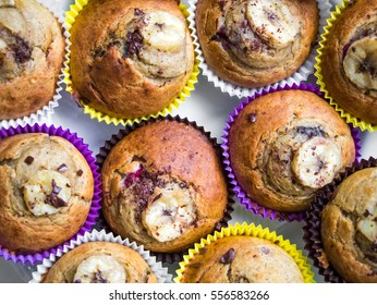 Homemade organic banana muffins in bright paper decorated with banana slice and chocolate crumb. Fresh cupcakes baked at home, tasty and beautiful. Top view, flat lay