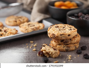 Homemade organic oatmeal cookies with raisins and apricots with baking tray on grey wood background. Black bowl of raisins and dried apricots