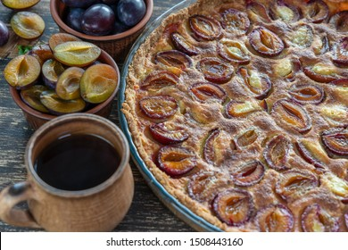 Homemade organic plum pie dessert ready to eat. Plum tart and cup hot tea on the old wooden background, close up