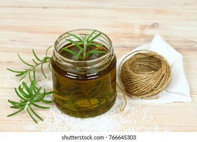 Homemade organic rosemary oil. Natural remedy, oil and fresh rosemary leaves on wooden background.