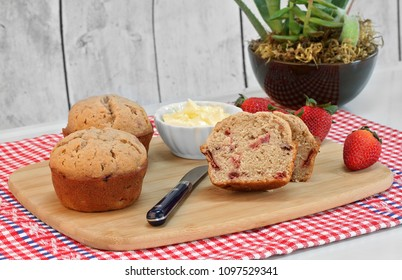 Homemade organic strawberry muffins, whole and cut, with fresh strawberries on a cutting board.  A bowl of whipped butter to the side.