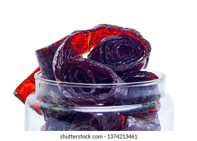 Homemade organic vegetarian natural pastille in glass bank. Slices of fruit paste in rolls. Delicious healthy candies made from berries and fruit. Isolated on white background. With clipping path.