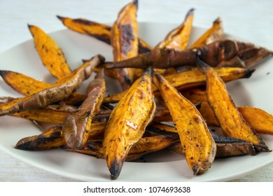 Homemade oven roasted sweet potato wedges closeup on white plate