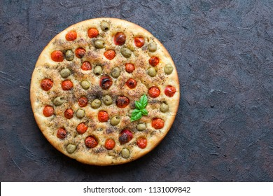 Homemade oven-baked  italian  focaccia - focaccia Barese, with olives, olive oil, tomatoes, herbs