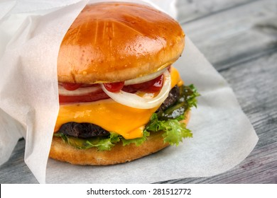 Homemade packed food , cheeseburger wrapped in paper on grey wooden surface
