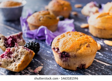 Homemade Paleo Muffins with almond flour, almond milk, coconut oil, vanilla, eggs, maple syrup and blackberries. Purple and blue background