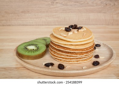 homemade pancake with kiwi raisins almond and butter on wood background