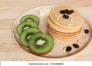 homemade pancake with kiwi raisins almond and butter on wood plate