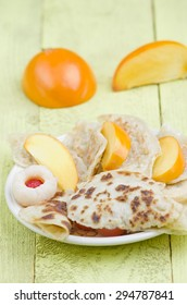 homemade pancake with lychee and persimmon on wooden, yellow background