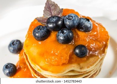 Homemade pancakes with apricot jam and blueberry on white background.