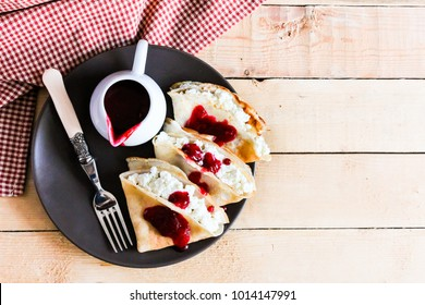 Homemade pancakes with cream cheese and berry jam on a plate, selective focus