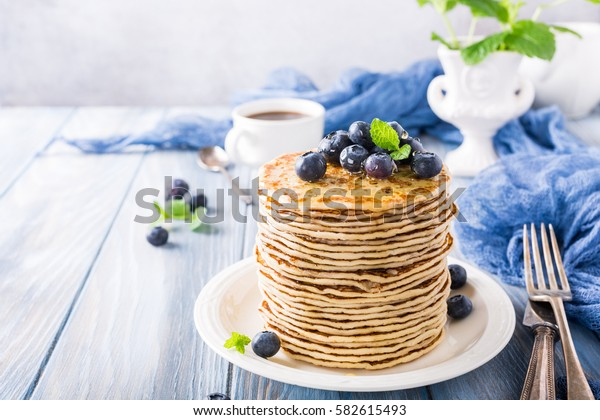 Homemade pancakes with fresh blueberries on a wooden background. Healthy breakfast concept.