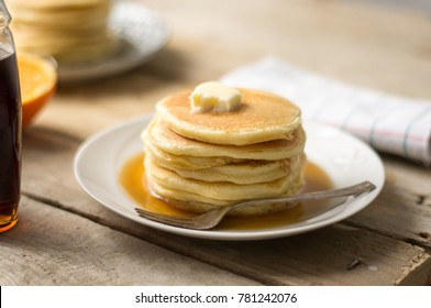 Homemade pancakes with maple syrup and butter on the wooden table with a cloth
