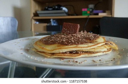 Homemade pancakes with nutella and half a walfer on top of it.