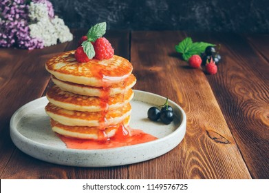 Homemade pancakes with raspberry jam, fresh berries and mint leaf on wooden table. Toned food photo.