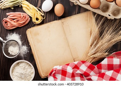 Homemade pasta cooking and vintage cooking book on wooden table. Top view with copy space