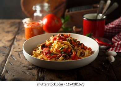 Homemade pasta with olives and tomato sauce, or Pasta alla puttanesca