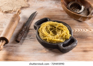 Homemade pasta is on the wooden dish