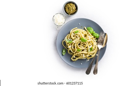 Homemade pasta, spaghetti, linguine with green pesto and basil over white. Italian healthy food concept with copy space, top view. Isolated.