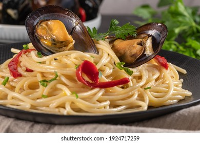 Homemade pasta spaghetti with mussels, peppers and parsley on rustic background. Sea food meal