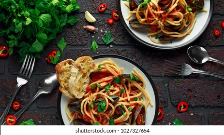 Homemade Pasta Spaghetti with mussels, tomato sauce, chilli and parsley on rustic background. sea food meal