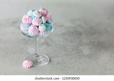 Homemade pastel pink, blue and white meringue in glass on neutral grey background. Horizontal minimalistic composition
