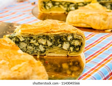 Homemade pastries with chicken meat on the table, pie with chicken and spinach.