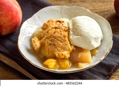 Homemade peach cobbler with vanilla ice cream over rustic wooden background - healthy pastry dessert