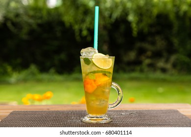 Homemade peach ice green tea with lime and lemon balm. On a wooden table outdoors in the garden. Healthy beverages concept.
