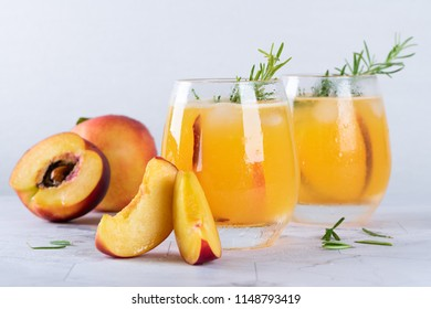 Homemade peach juice with ice cubes and rosemary leaves in glass