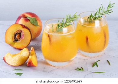 Homemade peach juice with ice cubes and rosemary leaves in glass on marble stone background