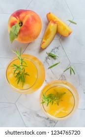 Homemade peach juice with ice cubes and rosemary leaves in glass on marble stone background. Flat layer