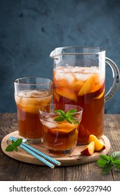 Homemade peach and lemon ice tea with mint on rustic background