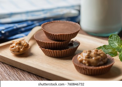 Homemade peanut butter cup, dark chocolate with caramel and bottle of milk, many protein. Dessert food.